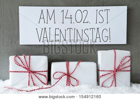 Label With German Text Am 14. Februar Ist Valentinstag Means February 14th Is Valentines Day. Three Christmas Gifts Or Presents On Snow. Cement Wall As Background. Modern And Urban Style.