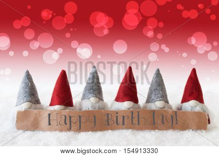 Label With English Text Happy Birthday. Christmas Greeting Card With Red Gnomes. Bokeh And Christmassy Background With Snow.