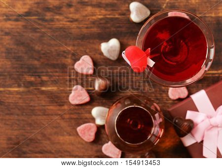 Alcoholic drinks for the festive party. Chocolate candy hearts. Gift for a holiday. Date on Valentines Day