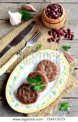Roasted bean cutlets with garlic and spices on plate. Small decorative barrel with uncooked red beans, garlic, parsley, fork, knife on old wooden background. Healthy vegetarian cutlets. Vintage style