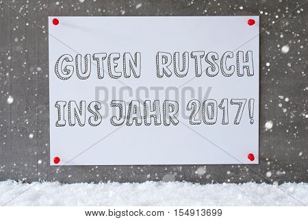 Label With German Text Guten Rutsch Ins Jahr 2017 Means Happy New Year 2017. Urban And Modern Cement Wall As Background On Snow With Snowflakes.