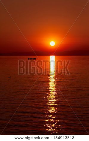 Beautiful red sunset at the sea. Big red sun over the sea. Silhouette of a fisherman in a boat on the surface of the sea sea gulls adorn the landscape.