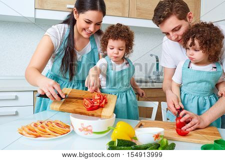 Happy Family With Twin Daughters In The Kitchen. Cheerful Mother, Father, Two Daughters, Twin Prepar