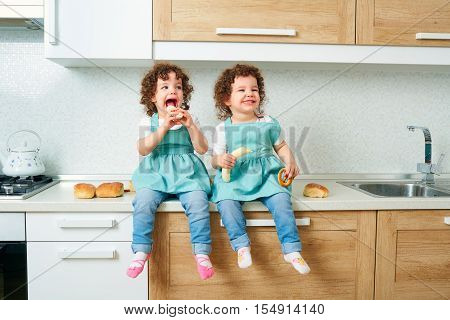 Children twins. Two little girls twins laugh and smile in the kitchen sitting on the table with food in their hands. Happy family happy children.