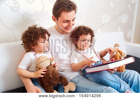 Dad with two daughters twins reading a book on the couch in the room. Teaching children to read. A happy family.