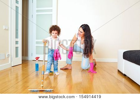 Mother with a child cleans the floor in the room. Mum learns the baby to clean the house. Parenting.