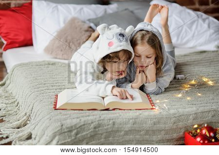 Christmas Holidays. Two children lie on the bed in soft pajamas. The bedroom is decorated with Christmas lights. Children read a huge book of Christmas stories. Merry Christmas and a Happy New Year. poster