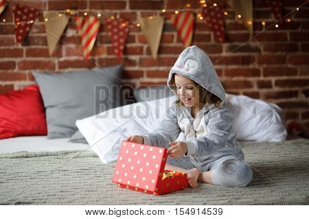 Christmas Holidays. Cute girl 8-9 years sits on a bed with a box in his hands. She received a Christmas gift. Bedroom decorated with Christmas garlands. Children adore Christmas and Christmas gifts.