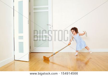 Little curly girl does the cleaning in the room.Child fun cleaning the floor mop and a rag in the house. Concept of cleanliness and order in the house. poster