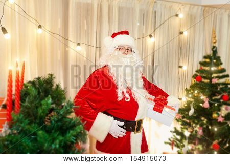 Santa Claus in a room decorated with a gift in hand on Christmas before the New Year is next to the fireplace with fire. The concept of the New Year and Christmas.