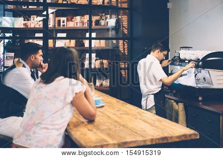 Back view of two customers sitting at table and looking at barista preparing coffee
