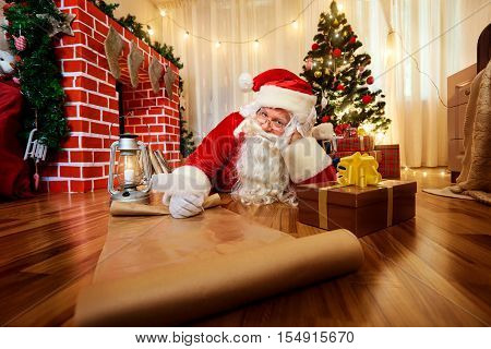 Santa Claus at Christmas New Year's Eve wrote a list of gifts to children on paper in the room with the Christmas tree and fireplace.