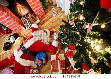 Santa Claus is sleeping tired drunk in a room near the fireplace and the Christmas tree after the New Year Christmas.