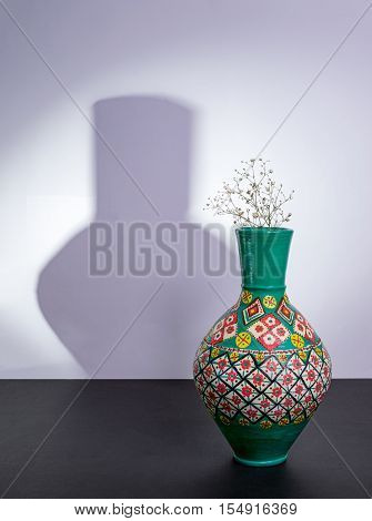 Colorful Egyptian traditional pottery vase small white flowers with harsh shadow excluding flowers shadow over black table and white wall