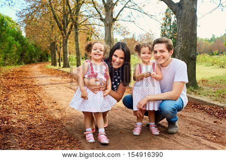Happy Family In The Park Summer Cuddling, Laughing And Smiling. Beautiful Curly Girl Twins In Dresse