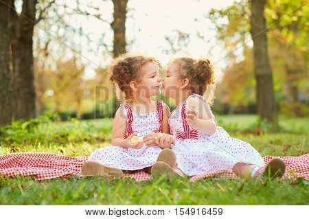 Sister сhildren Sitting On The Grass In A Park At A Picnic In The Sunshine Of The Evening Sun And A