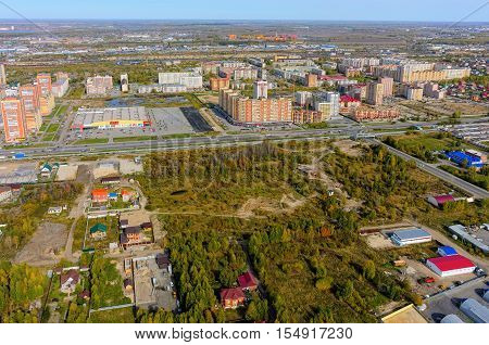 Tyumen, Russia - September 16, 2015: Okey shopping mall of household goods with a lot of parking space, East-2 residential district. Aerial view. Autumn