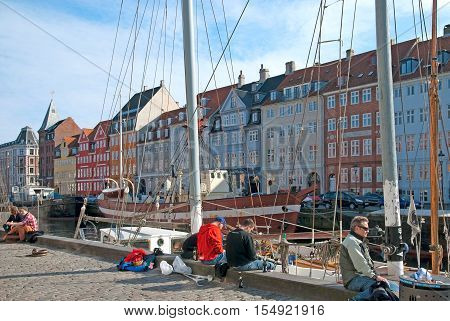 COPENHAGEN, DENMARK - APRIL 13, 2010: People sit on the embankment along Nyhavn. Nyhavn (New Harbour) is a 17th-century waterfront, canal and entertainment district in the center of the city