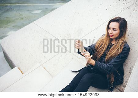 Beautuful smiling young teenage girl is sitting on the concrete steps and doing selfie photo. Student in alternative style clothes - black leather jacket and big boots. Copy-space area for your advertisement text or design