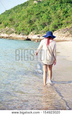 girl walks by the sea at Sai Kaew Beach Sattahip Chon Buri Thailand.