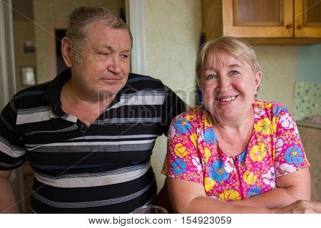 Affectionate grandparents having rest on kitchen at home, russian family