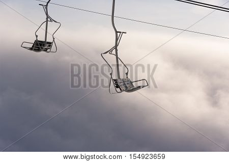 Chairlift above the clouds. Inversion in the mountains