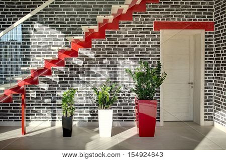Sunny room in a modern style with a black brick wall and light tiles on the floor. There is a red stair with a glass partition, plants in the multi-colored pots and a door. Horizontal.