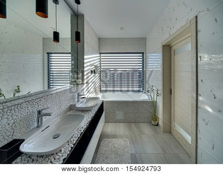 Light bathroom in a modern style decorated with the pebble. There is a bath, two sinks with faucets, big mirror, plant in the pot, window with blinds and a door. On the floor there is a bath carpet.