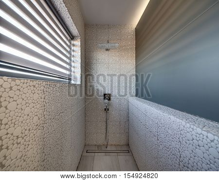 Bathroom in a modern style with decorative tiles and showers on the wall. There is a window with the blinds on the left. Sunlight falls through the blinds.