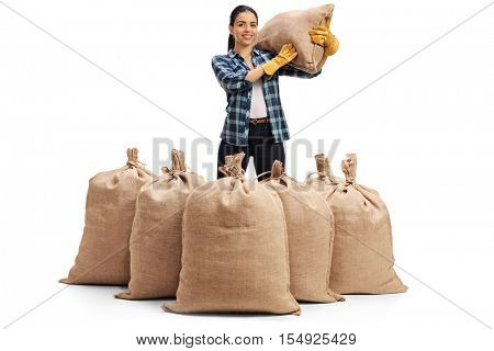Female agricultural worker standing behind burlap sacks and holding a sack on her shoulder isolated on white background
