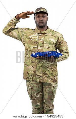 Portrait of soldier holding an american flag and saluting against white background