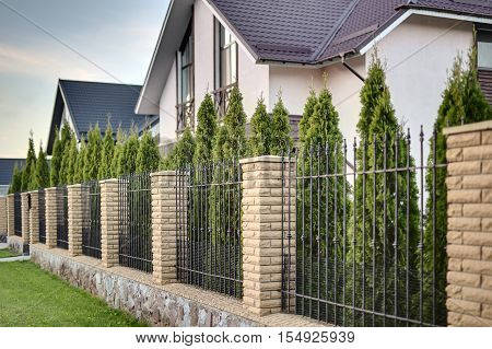 Metal fence with brick columns on the background of the line of green trees and country houses in a modern style. There is a lawn in front of it. Outside. Horizontal.