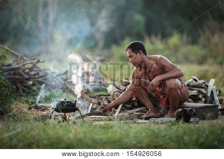The old man was boiling a kettle of water for tea in the traditional way of life in the countryside.