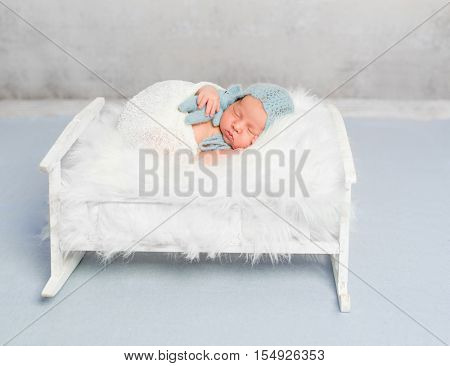 dreamy newborn boy holding toy sleeps on little bed covered with white fluffy blanket