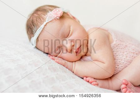 sweet face of a newborn girl with headband and flower on head sleeping on hand, close up