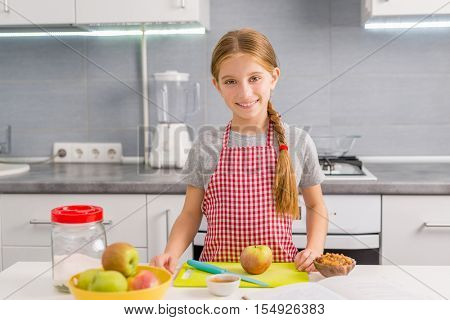 cute little girl preparing to cook apple strudel on kitchen with apples and knife on the table