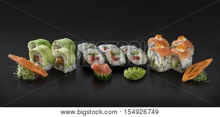 Fresh Sushi set. Uramaki and Hosomaki sushi rolls over black background