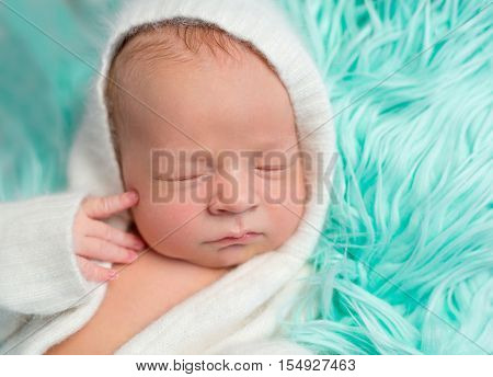 lovely dreamy newborn boy in white romper with hat on fluffy turquoise blanket, close up