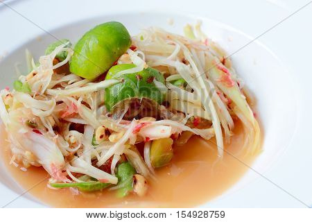Green Papaya Salad (som Tum Thai) In White Dish On Wood Table, Thai Cuisine Spicy Delicious