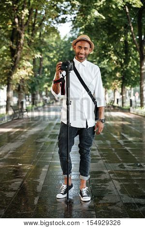 Full length portrait of black man in park. with camera and hat