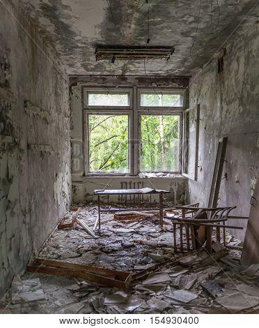 abandoned school study with debris and broken furniture in Pripyat