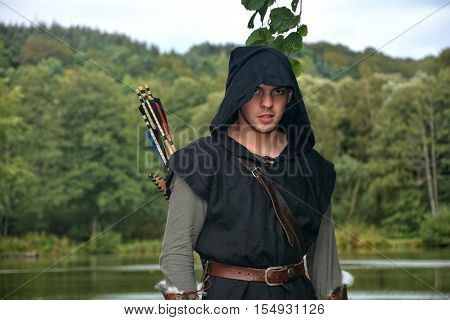 Medieval archer with black hood and coloured arrows in the quiver stands before a lake and looks forwards