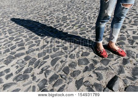 Female foot in torn jeans and red loafers close up