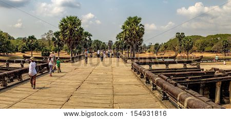 Siem Reap, Cambodia - February 1, 2016: Young tourists in front of the ruins and ancient pond of Angkor Wat temple Siem Reap Cambodia. The main road to Angkor Wat which runs tours