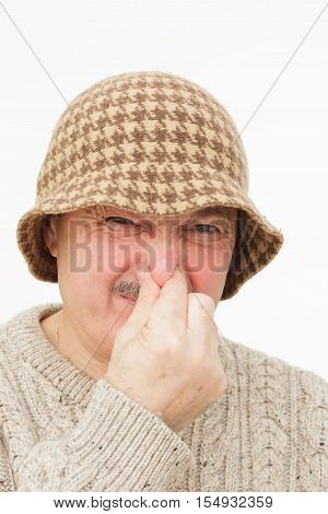 Unpleasant smell. Old man in hat plug nose