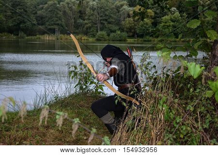 Medieval archer with black hood kneels on the ground before a lake, aims with arrow and curve forwards