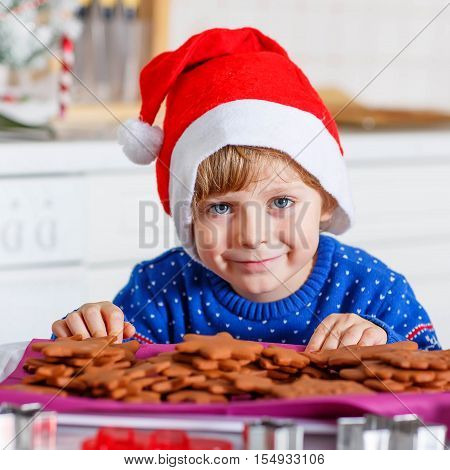 Funny kid boy in Santa Claus hat baking Christmas cookies at home. Adorable blond kid boy having fun. Traditional leisure with kids on Xmas. Family, holiday, kids lifestyle conceplt.