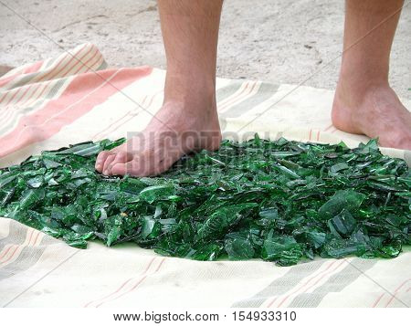 Barefooted human foot stepping on broken glass.