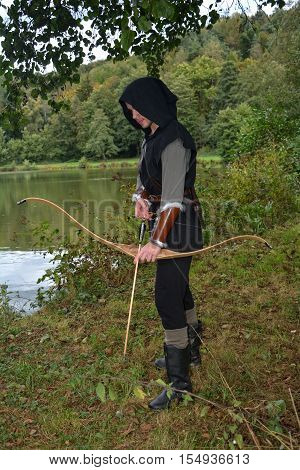 Medieval archer with black hood with the curve span before a lake