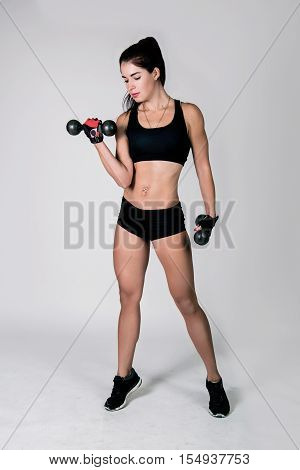 the sports girl in sportswear, practises with dumbbells